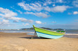 Fishing boat on the sand of Zimbros beach at dusk, calm sea and blue sky with clouds, Bombinhas, Santa Catarina