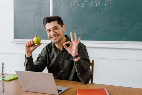 Fotografie, Obraz  smiling male teacher in glasses holding apple and showing ok sign at computer de