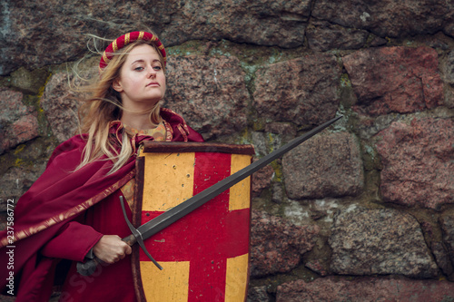 Foto  a brave young girl in a Burgundy Cape with a shield and a sword stands near the