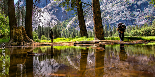 Photo  Two men by the reflective creek in Yosemite valley