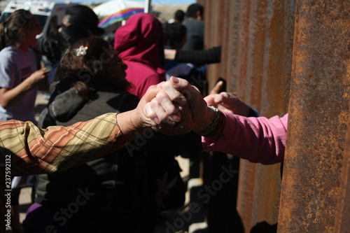 Fototapeta personas se saludan entre el muro que divide mexico de estados unidos