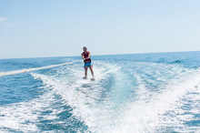 Young Man Glides On Water Skiing On The Waves On The Sea, Ocean. Healthy Lifestyle. Positive Human Emotions, Joy. Family Are Spending Time At Tropical Ocean In The Day Time. New Zealand.