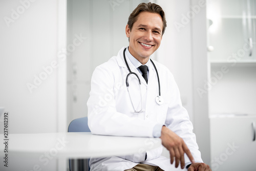 Emotional confident practitioner in white coat smiling and putting one hand on t Canvas Print