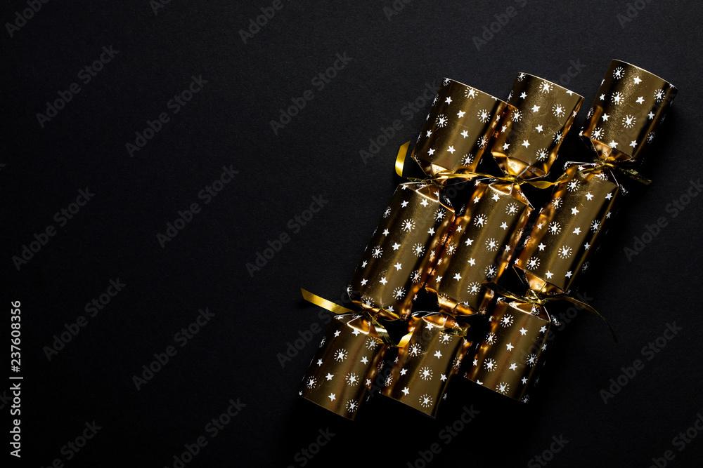 Fototapeta Gold festive Christmas crackers on a dark background