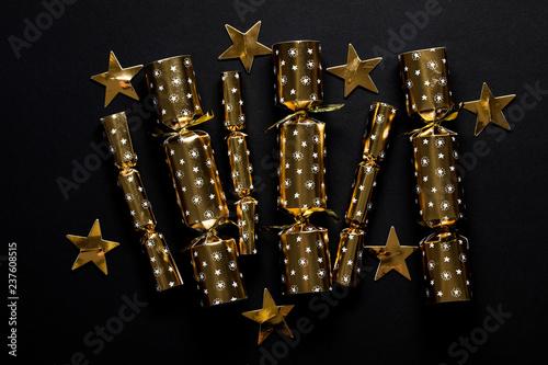 Fototapeta Gold festive Christmas crackers on a dark background obraz na płótnie