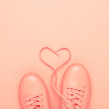 Pair Of Coral Shoes With Heart Made Of Shoelaces On Coral Background. Trendy Pastel Color, Monochrome Image. Living Coral Color Of The Year 2019.