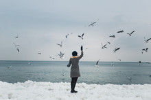 Girl Feeding Seagulls On The Frozen Bank Of The Winter Sea