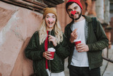 Waist up portrait of charming girl in hat and handsome bearded guy demonstrating red and pink paper hearts. They holding cups of coffee and smiling