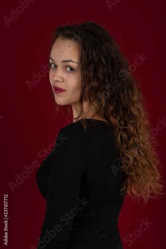 d1eac86a80 Waist up portrait of a young woman wearing black dress with long curly hair  on a dark burgundy background in the studio