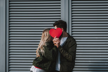 Beautiful Young Couple Covering Faces With Red Paper Heart