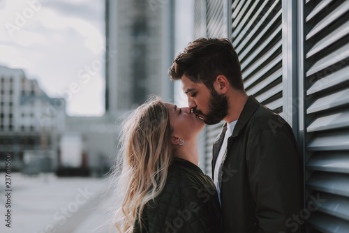Beautiful young couple kissing tenderly on the street Fototapeta