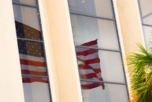 Reflection Of American Flag On Window Of A Building