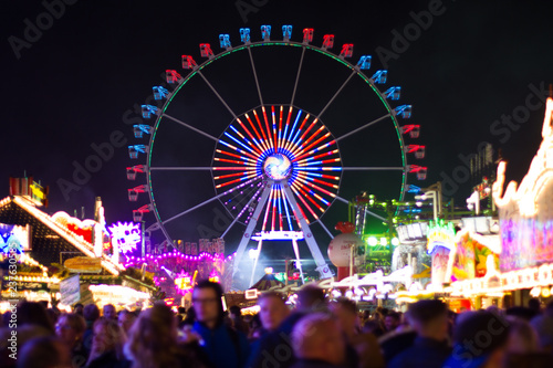 Foto op Aluminium Carnaval ferris wheel at night with blurry crowd in the foreground