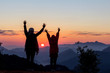 Silhouettes of happy mother and daughter with raised hands looking morning sunrise on peak of mountain.