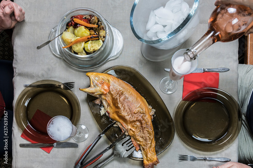 two people drink rose wine while eating baked trout