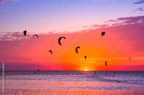 Foto auf AluDibond Hochrote Kite-surfing against a beautiful sunset. Many silhouettes of kites in the sky. Holidays on nature. Artistic picture. Beauty world.