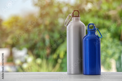 Sports water bottles on table against blurred background. Space for text