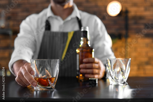 Poster Cocktail Bartender with glass and bottle of whiskey at counter in bar, closeup. Space for text