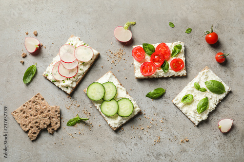 Tasty snacks with cream cheese and vegetables on gray table, flat lay