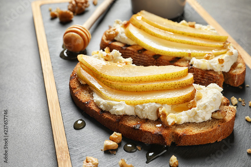 Toasted bread with cream cheese and pear on board