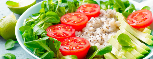 Fototapeta Oatmeal porridge with avocado and vegetable salad of fresh tomatoes and lettuce. Healthy dietary breakfast. Banner