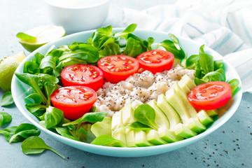 Fototapeta Oatmeal porridge with avocado and vegetable salad of fresh tomatoes and lettuce. Healthy dietary breakfast