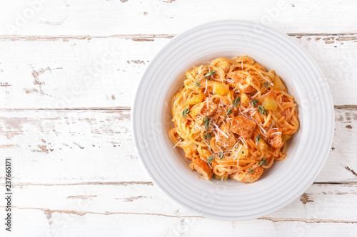 Spaghetti bolognese pasta with tomato sauce, vegetables and chicken meat on white wooden rustic background. Traditional italian food. Top view. Flat lay