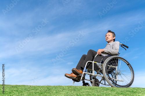 Fényképezés  青空バックを背景に車イスに座るシニア男性。福祉、介護、病気、障害者、老後イメージ
