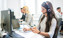 Friendly Customer Support Female Operator With Headphones Writing Notes To Notebook Taken From Smartphone At Office