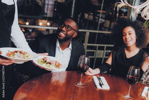 Valokuva  Waiter Serving Salad to African Couple Restaurant