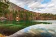 Autumn sunrise on the lower lake of Fusine. Explosion of colors