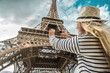 Woman tourist selfie near the Eiffel Tower in Paris under sunlight