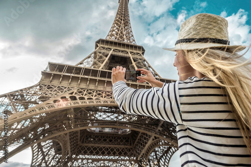 Fotografia Woman tourist selfie near the Eiffel Tower in Paris under sunlight