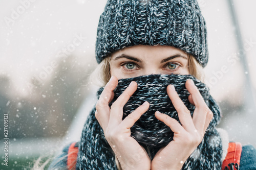 Fotomural portrait of young blonde woman closing face with winter scarf feeling cold under