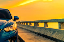 Luxury Blue SUV Car With Sport And Modern Design Parked On Concrete Road By The Sea At Sunset. Hybrid Auto And Automotive Concept. Road Trip And Car Driving For Travel. Electric Car Technology Concept