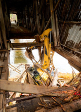 Large Construction Equipment Crashed Through The Bottom Of A Wooden Covered Bridge. The Arm And Backhoe Are Snagged Over A Wooden Beam. Lots Of Wood Debris. River Flows Below. Identifying Marks Rem