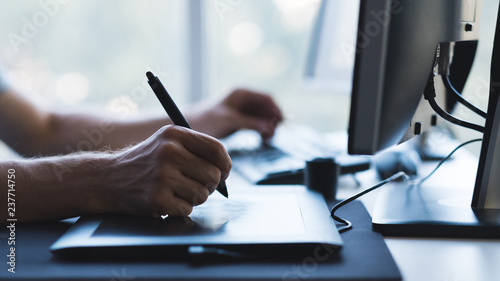 man hands drawing on graphic tablet with stylus. designer or digital artist at work
