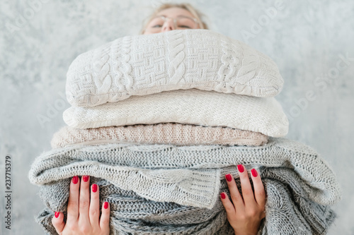 Obraz woman holding big stack of knitted plaids and blankets. cozy and warm winter home decor - fototapety do salonu