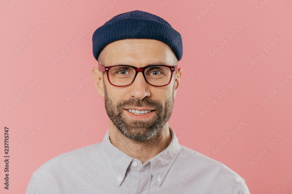 Fototapety, obrazy: Close up portrait of smiling unshaven male, rejoices good news, wears hat and shirt, looks with eyes full of joy isolated over pink background. European man with bristle ready for date with girlfriend