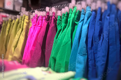 Photo sur Aluminium Aquarelle avec des feuilles tropicales Fashion clothes on clothing rack - bright colorful closet. Closeup of rainbow color choice of trendy female wear on hangers in store closet or spring cleaning concept.