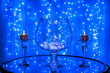 Glass vase garland with round candles on blurred blue background