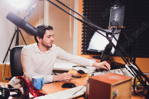 Fotografia, Obraz  Portrait of handsome young latin man sitting in front of a microphone with laptop at radio station