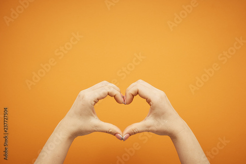 Valokuva  gesture female hand holding a heart from his fingers , isolated on orange backgr