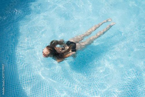 sexy girl takes a sunbath in the swimming pool