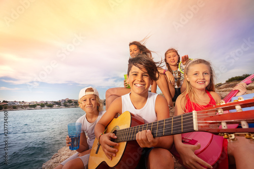 Foto Young friends with guitar having fun outdoors
