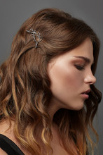 Close Up Portrait Of A Young Brunette Lady With Natural Make-up And Wavy Hairstyle. Her Tresses Are Adorned With Silver Twig Hair Clip. The Side View Of The Girl Posing Against The Grey Background.