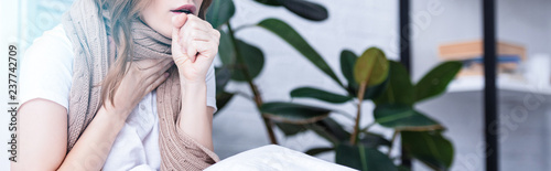 panoramic view of sick woman coughing at home