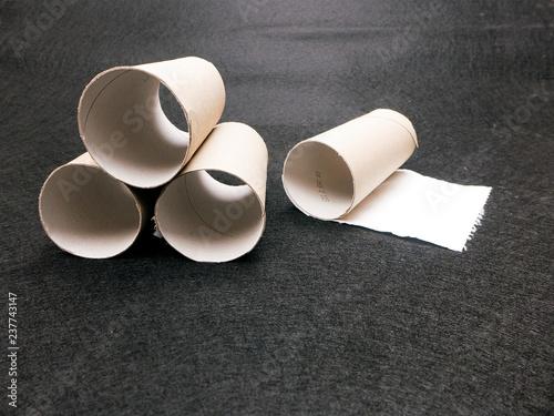 Fotografía  vier leere Papprollen liegen vor schwarzen Hintergrund