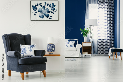 Photo Floral accents in bright living room interior in blue and white colors, real pho
