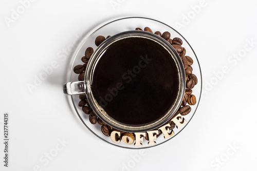 Wall Murals Cafe A glass cup of coffee with coffee beans and letters on them on a white background from the top